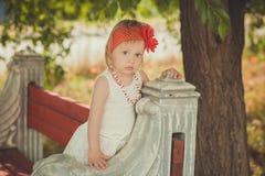 Retro- stilvolles gekleidetes blondes junges Babykind, aufwerfend in Central- Parkgarten, den couturer weißes Kleidroten Bandana  Stockbild