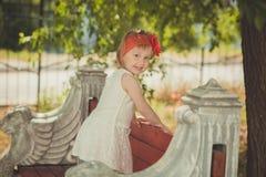 Retro- stilvolles gekleidetes blondes junges Babykind, aufwerfend in Central- Parkgarten, den couturer weißes Kleidroten Bandana  Lizenzfreie Stockfotos