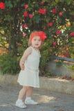 Retro- stilvolles gekleidetes blondes junges Babykind, aufwerfend in Central- Parkgarten, den couturer weißes Kleidroten Bandana  Lizenzfreies Stockbild
