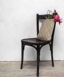 Retro stol i tomt rum med sugrörpåsen och blommor Arkivbild