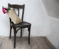 Retro stol i tomt rum med sugrörpåsen och blommor Arkivbilder