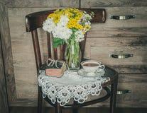 Retro stol med blommor i en vas, en gammal bönbok och en kopp te arkivfoton