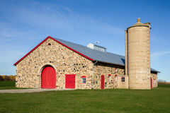 Retro Stone Barn with Bright Red Doors Stock Images
