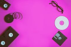 Retro storage devices: plate, two videocassette, floppy disk, CD and glasses. Outdated technology concept on pink paper background royalty free stock image