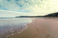Retro strand med den fotspårplatsCayton fjärden Arkivbild