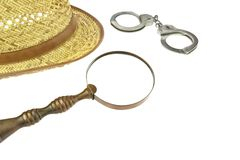 Retro Straw Hat, Magnifying Glass and Handcuffs Stock Photography