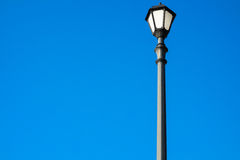 Retro street lamp on the blue background. Street lamp on a bright blue background. Black lantern in vintage style, photographed in the morning sunshine. Bottom Stock Photography