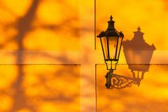 The retro street light on the wall at sunset. Detail of retro street light on the wall at sunset. Prague, Czech Republic royalty free stock photography