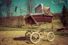 Retro style baby carriage outdoors on sunny day. Retro style stroller baby carriage outdoors in nature on sunny day with retro vintage green instagram like Royalty Free Stock Image