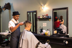 Retro Style Barber Shop. Auckland, New Zealand - February 17, 2017: A barber is making a haircut with a clipper for a customer inside a retro style barbershop Royalty Free Stock Images