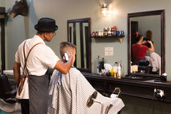 Retro Style Barber Shop. Auckland, New Zealand - February 17, 2017: A barber is making a haircut with a clipper for a customer inside a retro style barbershop Stock Image