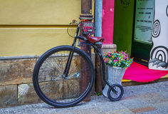 Retro style bicycle and basket with colorful artificial flowers Royalty Free Stock Photo