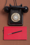 Retro style black russian dial telephone and notebook Royalty Free Stock Photography