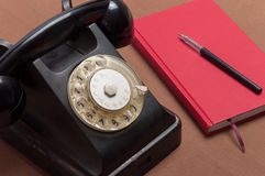 Retro style black russian dial telephone and notebook Stock Photos