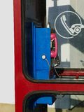 Retro style blue land line public telephone in red booth. Retro style blue and pink land line public telephone in red phone booth in daylight with shadow and royalty free stock photos