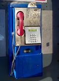 Retro style blue and pink land line public telephone. In red phone booth in daylight with shadow and phone symbol on glass royalty free stock photo