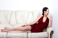 Retro style brunette woman lying on sofa Stock Image