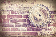 Retro style circular saw blade on brick wall. Stock Image