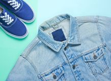 Retro style denim stylish jacket and hipster sneakers. On a mint-colored paper background. Minimalism, top view,flat lay stock images