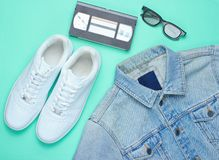 Retro style denim stylish jacket, video cassette, 3d glasses. And white hipster sneakers on a mint-colored paper background. Minimalism, pop culture, top view stock photo