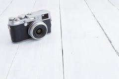 Retro style digital camera on wooden background Stock Image