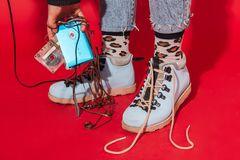 Retro style fashionable woman. New trend back to 90s. Retro styled fashionable woman in sport jacket and jeans with vintage cassette player on red background stock photography