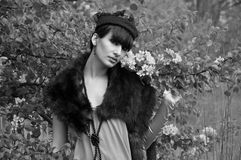 Retro style girl. Black and white photograph of pretty young fashion woman wearing such retro-styled clothes as gloves, fur boa and tablet and standing near Stock Images