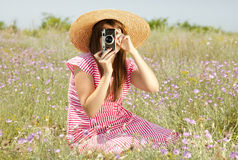 Retro style girl at countryside with camera.  Royalty Free Stock Photography