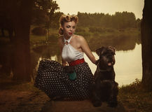Retro style. The girl with a dog in a park in sunset rays. Royalty Free Stock Image