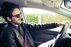 Retro style of handsome man with sun glasses smiling happy driving Stock Image