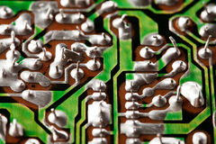 Retro style hardware technology concept with green circuit board. Macro view electronic chip soldering paths and trace Royalty Free Stock Photography