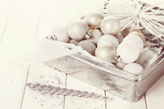 Retro style image of Christmas ornaments. Retro style image of  silver Christmas ornaments in a silver box over white wooden background. Selective focus, shallow Royalty Free Stock Image