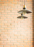 Retro style incandescent bulb lamp in vintage coffee shop with brick wall background Stock Photos