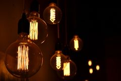 Retro style light bulbs glowing. Vintage old style light bulbs glowing on dark background Stock Image