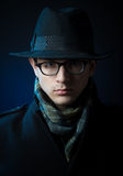 Retro style male portrait. Portrait of a young man in the black trench coat, hat and glasses standing in the darkness Royalty Free Stock Photography