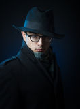 Retro style male portrait. Portrait of a young man in the black trench coat, hat and glasses standing in the darkness Stock Photos