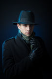Retro style male portrait. Portrait of a young man in the black trench coat and hat standing in the darkness Royalty Free Stock Photos