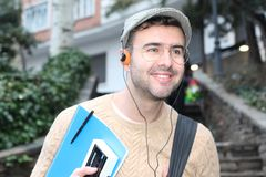 Retro style male student listening to music.  Stock Image