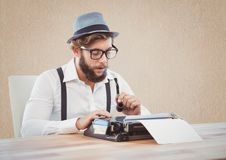 Retro style man holding smoking pipe and using a typewriter. At desk Royalty Free Stock Images