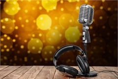 Retro style microphone and headphones on wooden. Style retro mic microphone headphones background holiday Stock Photos