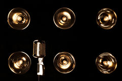 Retro style microphone. Old retro microphone on a background of black wall with incandescent Stock Photography