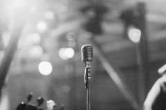 Retro style microphone on a pole in a concert. Guitarist in foreground Stock Photos