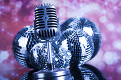 Retro style microphone on sound waves and Disco Balls Royalty Free Stock Photos