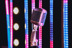 Retro style microphone on stage in the spotlight performance of the musical group. Royalty Free Stock Photography