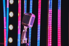 Retro style microphone on stage in the spotlight performance of the musical group. Stock Photo