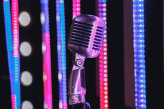Retro style microphone on stage in the spotlight performance of the musical group. Royalty Free Stock Photos