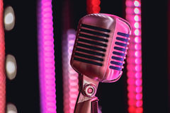 Retro style microphone on stage in the spotlight performance of the musical group. Royalty Free Stock Photo