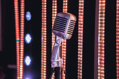 Retro style microphone on stage in the spotlight performance of the musical group. Royalty Free Stock Image