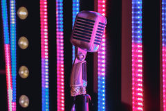 Retro style microphone on stage in the spotlight performance of the musical group. Royalty Free Stock Images