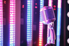 Retro style microphone on stage in the spotlight performance of the musical group. Stock Photography